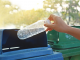 Bottle being put into recycling bank